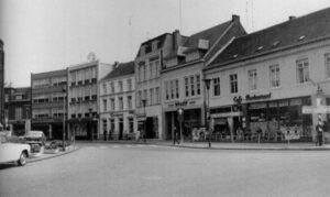 Van rechts naar links: Le Coq d'Or (was Hundtscheid), in hetzelfde pand vervolgens Heitkönig, later Witteveen en een uitzendbureau. Dan naaimachinehandel Pfaff van Schluyper. Hiervoor zat Krekelberg in het pand. Vervolgens Valderop. Dat werd later de Blauwe Reiger. In de eerste helft van de 20ste eeuw zaten hier de dames Knops met mode artikelen. Het grote pand wad van Penners en dan zie je de passage.